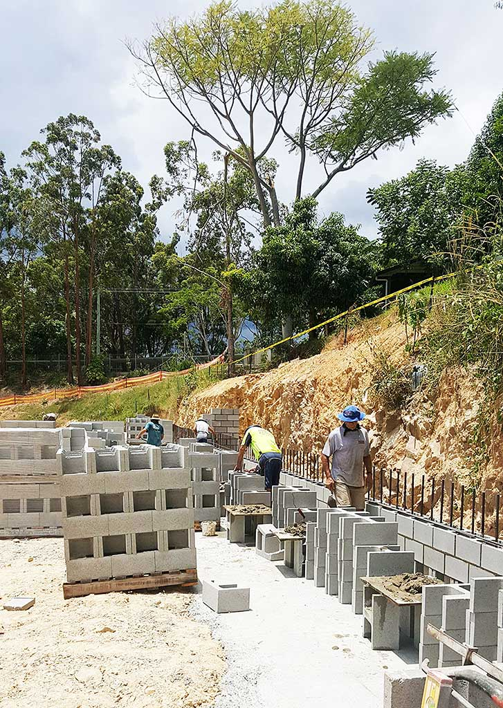 The retaining walls at the new high school construction site receive close attention.